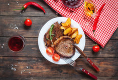 Grilled beef steak seasoned with spices served on a wooden board with fresh cherry tomato, baked potatoes and red hot chili pepper. S Stock Image