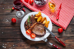 Grilled beef steak seasoned with spices served on a wooden board with fresh cherry tomato, baked potatoes and red hot chili pepper Stock Photos