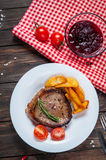 Grilled beef steak seasoned with spices served on a wooden board with fresh cherry tomato, baked potatoes and red hot chili pepper. S Royalty Free Stock Photography