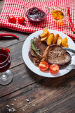 Grilled beef steak seasoned with spices served on a wooden board with fresh cherry tomato, baked potatoes and red hot chili pepper. S Stock Photo