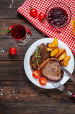 Grilled beef steak seasoned with spices served on a wooden board with fresh cherry tomato, baked potatoes and red hot chili pepper Stock Photo