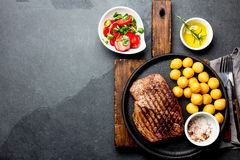 Grilled beef steak served on cast iron plate with tomato salad and potatoes balls. Barbecue, bbq meat beef tenderloin. Top view, slate background stock image