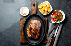Grilled beef steak served on cast iron plate with tomato salad and potatoes balls. Barbecue, bbq meat beef tenderloin. Top view, slate background stock photo