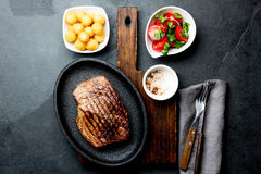 Grilled beef steak served on cast iron plate with tomato salad and potatoes balls. Barbecue, bbq meat beef tenderloin. Top view, slate background royalty free stock photo