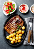 Grilled beef steak served on cast iron plate with tomato salad and potatoes balls. Barbecue, bbq meat beef tenderloin. Top view, slate background royalty free stock photos