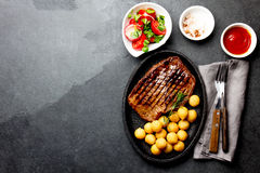 Grilled beef steak served on cast iron plate with tomato salad and potatoes balls. Barbecue, bbq meat beef tenderloin. Top view, slate background stock photography
