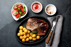 Grilled beef steak served on cast iron plate with tomato salad and potatoes balls. Barbecue, bbq meat beef tenderloin. Top view, slate background royalty free stock images