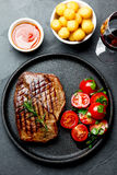 Grilled beef steak served on cast iron plate with tomato salad, potatoes balls and red wine. Barbecue, bbq meat beef. Tenderloin. Top view, slate background royalty free stock photo
