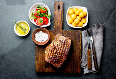 Grilled beef steak served on wooden table with tomato salad and potatoes balls. Barbecue, bbq meat beef tenderloin. Top. View, slate background stock photos