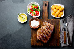 Grilled beef steak served on wooden table with tomato salad and potatoes balls. Barbecue, bbq meat beef tenderloin. Top. View, slate background royalty free stock photography