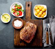 Grilled beef steak served on wooden table with tomato salad and potatoes balls. Barbecue, bbq meat beef tenderloin. Top. View, slate background stock photo