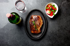 Grilled beef steak served on wooden table with tomato salad and red wine. Barbecue, bbq meat beef tenderloin. Top view Royalty Free Stock Photography