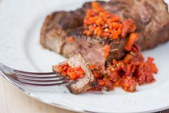 Grilled beef steak, slice on fork with tomato salsa sauce stock image