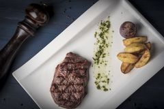 Grilled beef steak with souce, baked potato and onion on white plate with pepper stock photography