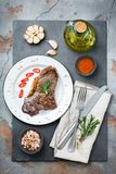 Grilled beef steak with spices ready for dinner. Food and drink concept. Grilled beef steak with spices ready for dinner on a dark table background. Flat lay top Stock Photography