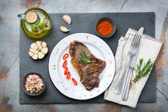 Grilled beef steak with spices ready for dinner. Food and drink concept. Grilled beef steak with spices ready for dinner on a dark table background. Flat lay top Stock Images