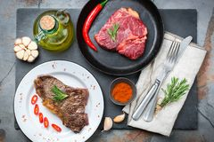 Grilled beef steak with spices ready for dinner. Food and drink concept. Grilled and raw beef steak with spices ready for dinner on a dark table background. Flat Stock Image