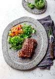 Grilled beef steak tenderloin on gray stone plate with salad and chimichurri sauce.  stock images