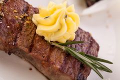 Grilled beef steak topped with butter and rosemary Royalty Free Stock Images