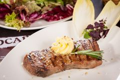 Grilled beef steak topped with butter and rosemary Royalty Free Stock Photos