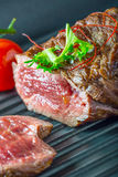 Grilled Beef steak with vegetable decoration. Grilled porterhouse steak on slate board. Royalty Free Stock Photo