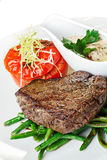 Grilled beef steak. With vegetable garnish. Hearty steak dinner Stock Images