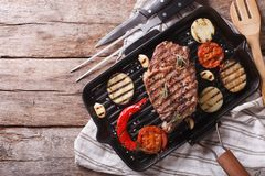 Grilled beef steak with vegetables in pan. horizontal top view Royalty Free Stock Images
