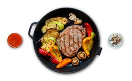 Grilled beef steak and vegetables in pan isolated. Grilled beef steak and roasted vegetables isolated on white background. Juicy meat dish with sauce, rosemary Stock Images