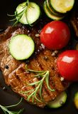 Grilled beef steak with vegetables . Top view. Grilled beef steak with tomatoes, zucchini and fresh herbs. Top view stock photo