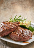 Grilled beef steak on white plate. Grilled beef steak and zucchini on white plate Royalty Free Stock Photos