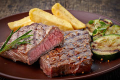 Grilled beef steak. On wooden cutting board Royalty Free Stock Image