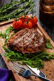 Grilled beef steak on wooden cutting board. Stock Images