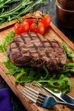 Grilled beef steak on wooden cutting board. Stock Photography