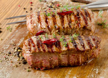 Grilled Beef steak on   wooden cutting board . Royalty Free Stock Images