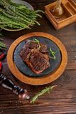 Grilled beef steak in round wooden tray on old table, top view royalty free stock photo