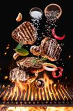 Grilled beef steaks with vegetables and spices fly over the glowing grill barbecue fire royalty free stock image