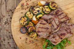Grilled beef steaks with vegetables. Grilled beef steak with vegetables on the wooden plate Royalty Free Stock Photo