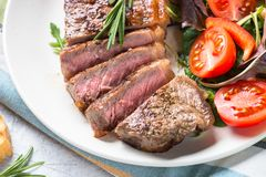 Grilled beef striploin steak with fresh salad. Healthy food lunch menu. Close up Royalty Free Stock Photography