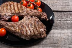 Grilled beef tomahawk steak. BBQ food background in plate stock photos