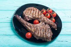 Grilled beef tomahawk steak. BBQ food background in plate stock photography