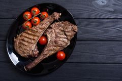 Grilled beef tomahawk steak. BBQ food background in plate royalty free stock photography
