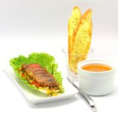Grilled Beef and Tomato Soup. Grilled Sliced Beef on a bed of lettuce and vegetable salsa served with tomato soup and garlic bread Royalty Free Stock Photos