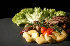 Grilled Beef and Vegetables. A display of grilled beef and vegetables on a black background stock photos