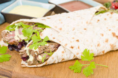 Grilled Beef Wraps. Griddled sirloin steak, sliced and wrapped in a flatbread served with blue cheese sauce and salad. Close up royalty free stock photo