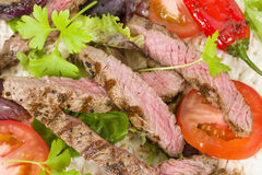 Grilled Beef Wraps. Griddled sirloin steak, sliced and wrapped in a flatbread served with salad. Close up stock photo