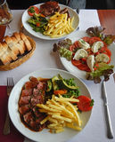 Grilled beefsteak, french fries and vegetables Royalty Free Stock Image