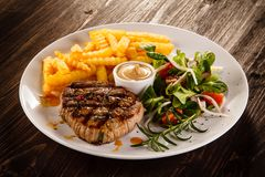 Grilled beefsteak with french fries. On wooden table stock image