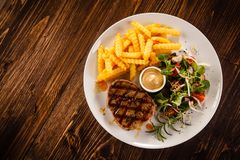 Grilled beefsteak with french fries. On wooden table royalty free stock photo