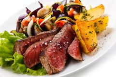 Grilled beefsteak with potatoes. On white background stock photography