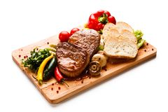 Grilled Beefsteak With Toasts On Wooden Board Royalty Free Stock Photos